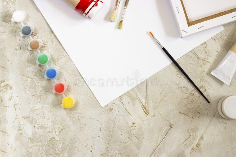 Flatlay com pinturas brilhantes em uns recipientes redondos pequenos e umas muitas paletas, lona, escova e folha de papel branca  fotografia de stock royalty free