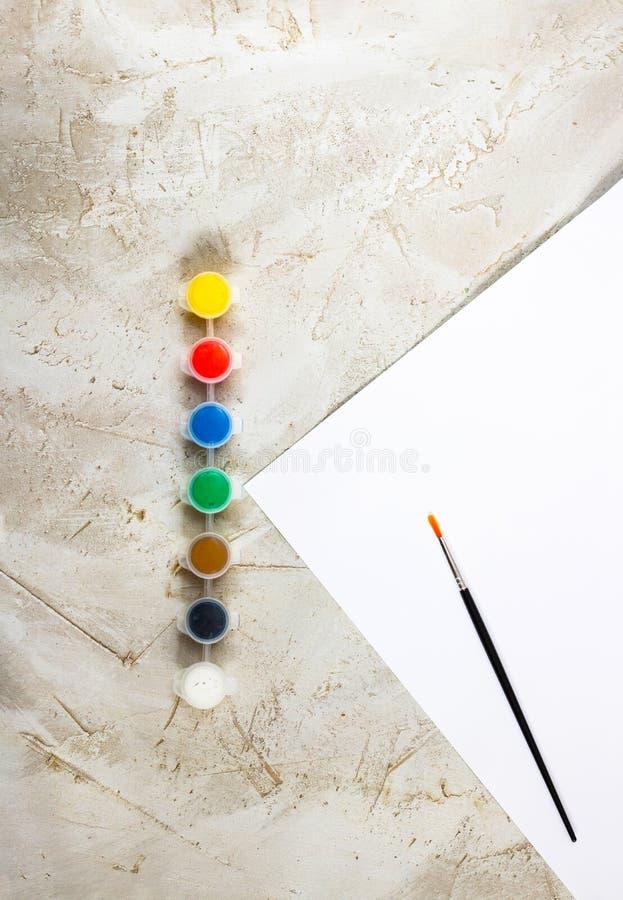 Flatlay com pinturas brilhantes em uns recipientes redondos pequenos, em uma escova e na folha de papel branca no backcground cin fotografia de stock