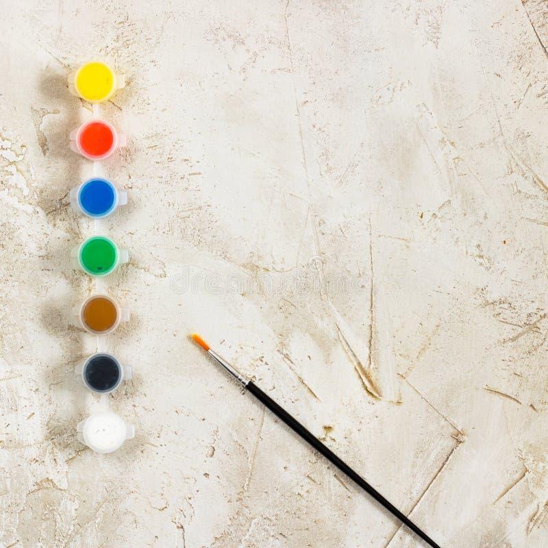 Flatlay com pinturas e a escova brilhantes no fundo cinzento do cimento, artista, desenho, passatempo, arte imagem de stock