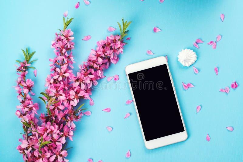 Flatlay com zombaria do smartphone acima e flores Teste padrão floral no fundo azul Vista superior Floresce a composição Fundo da foto de stock royalty free