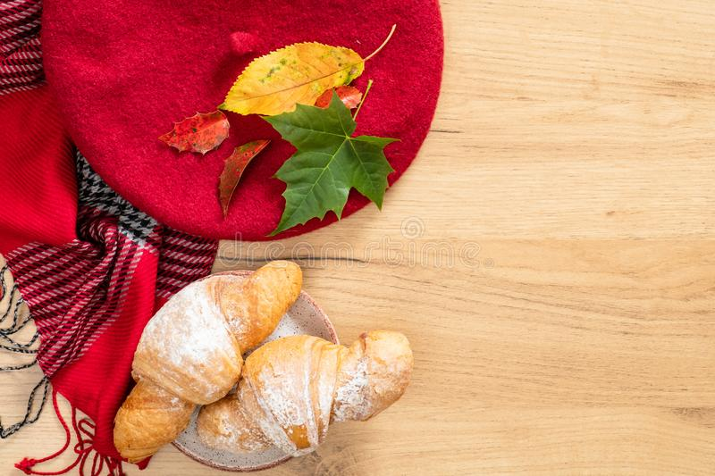 Flatlay composition with autumn fallen leaves, feminine wool scarf, red beret cap, croissants. Cozy home, autumn desk table royalty free stock photo