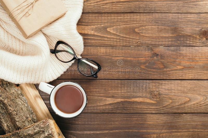 Flatlay composition with red scarf, cup of tea, firewood, book on wooden desk table. Hygge style, cozy autumn or winter holiday royalty free stock photo