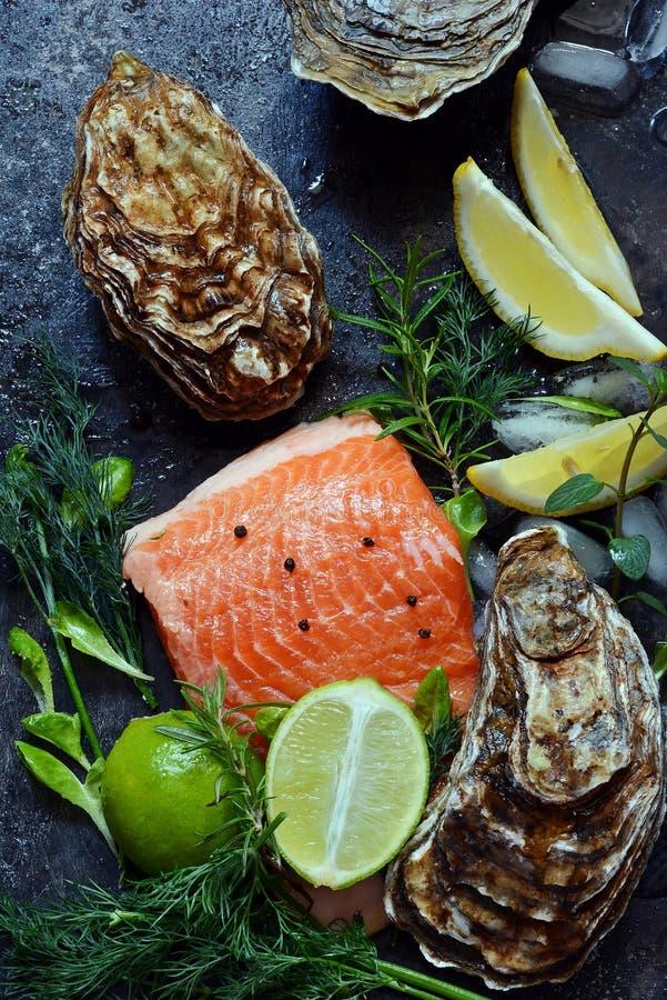 flatlay Composizione di frutti di mare freschi su un fondo scuro Trota ed ostriche con le erbe ed il limone immagini stock