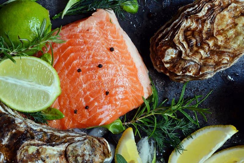 flatlay Composizione di frutti di mare freschi su un fondo scuro Trota ed ostriche con le erbe ed il limone fotografie stock libere da diritti