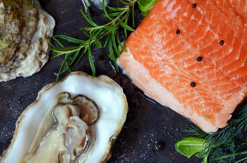 flatlay Composizione di frutti di mare freschi su un fondo scuro Trota ed ostriche con le erbe ed il limone immagine stock