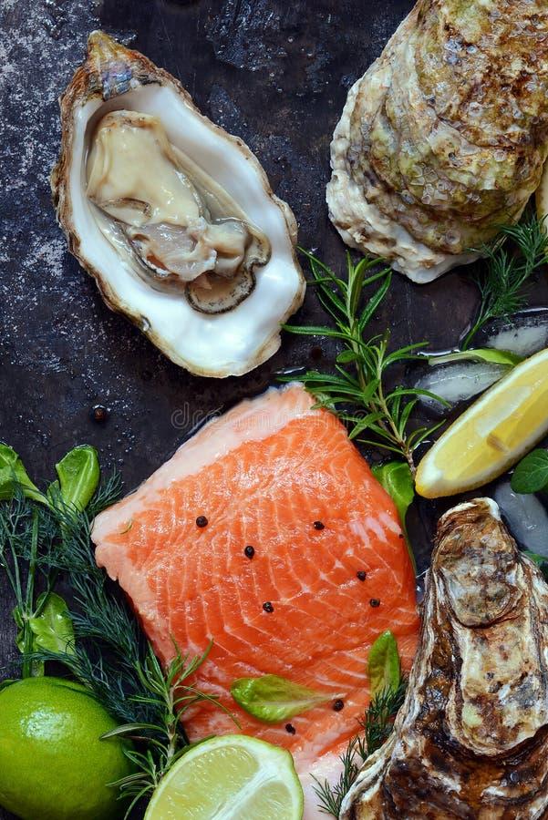 flatlay Composizione di frutti di mare freschi su un fondo scuro Trota ed ostriche con le erbe ed il limone fotografia stock libera da diritti