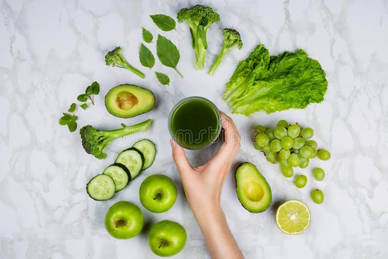 Flatlay con la mano del ` s della donna che raggiunge per il succo verde circondato dalla frutta e dalle verdure verdi fotografia stock libera da diritti