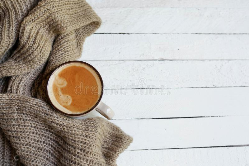 Flatlay with cup of coffee in scarf on white wooden background, autumn or winter concept stock image