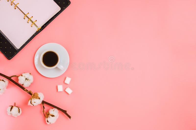 Flatlay with cup of espresso, cotton branch, sugar cubes and planner, royalty free stock photos