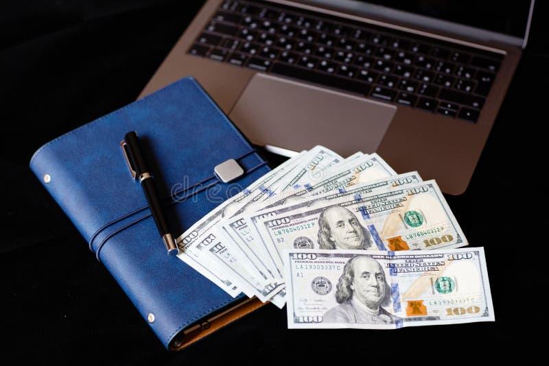 Flatlay da tavolino: computer portatile, taccuino, penna e denaro contante trovantesi sul fondo nero Finanza, lavoro e concetto d fotografia stock libera da diritti