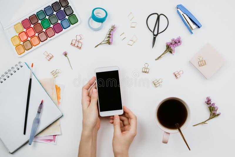 Flatlay degli acquerelli, spazzole, sketchbook con la pagina in bianco, tazza di tè, smartphone con lo schermo nero immagine stock