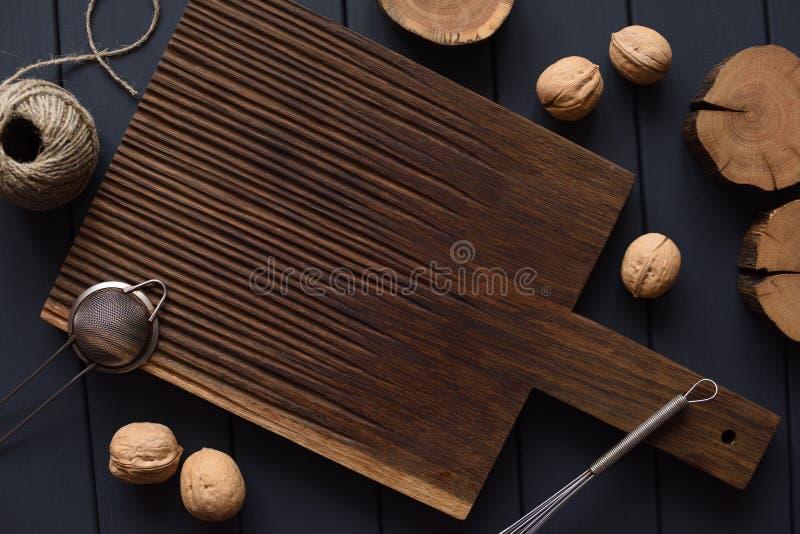 Flatlay del tablero oscuro del roble, de las losas de madera, de las nueces y de los utensilios de la cocina como fondo para la c fotos de archivo
