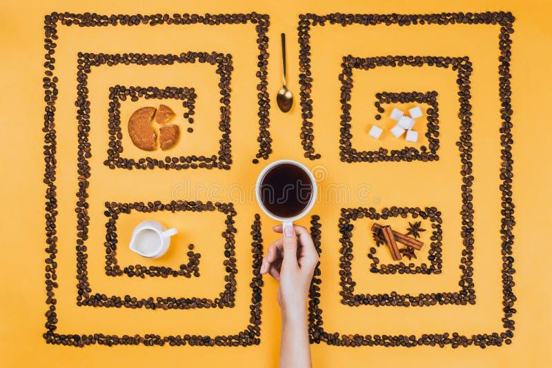 Flatlay der Kaffeetasse mitten in Muster oder des Labyrinths gemacht von den Kaffeebohnen lizenzfreie stockfotos