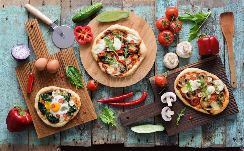 Flatlay der Pizza-Party Selbst gemachte Pizzas und rohes Gemüse in AB lizenzfreie stockbilder
