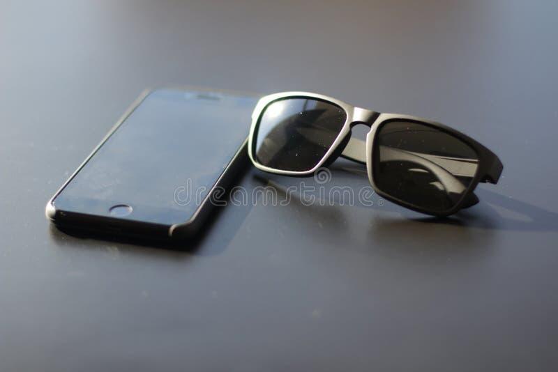 Flatlay der schwarzen Sonnenbrille und des schwarzen Telefons stockfoto