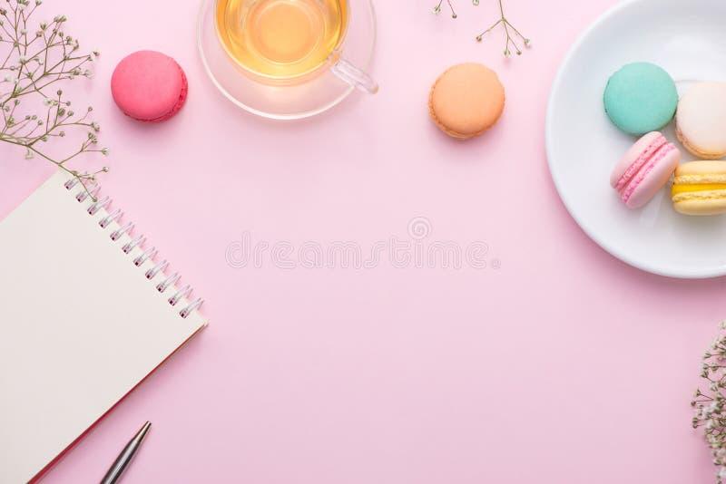 Flatlay des Notizbuches, Kuchen macaron, Tasse Tee und Blume auf Rosa lizenzfreie stockfotos