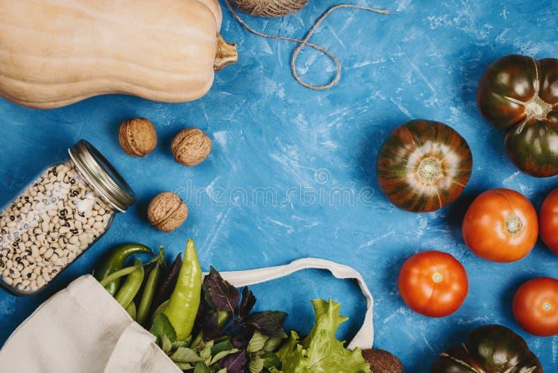 Flatlay dos tomates, dos verdes, da abóbora, da corda e dos feijões em um frasco no fundo azul imagem de stock