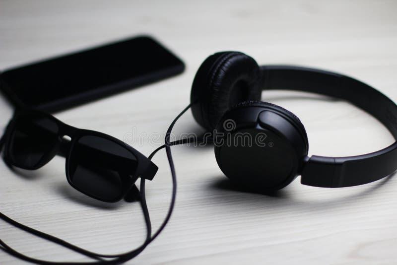Flatlay du téléphone, des écouteurs et du verre noirs photographie stock libre de droits