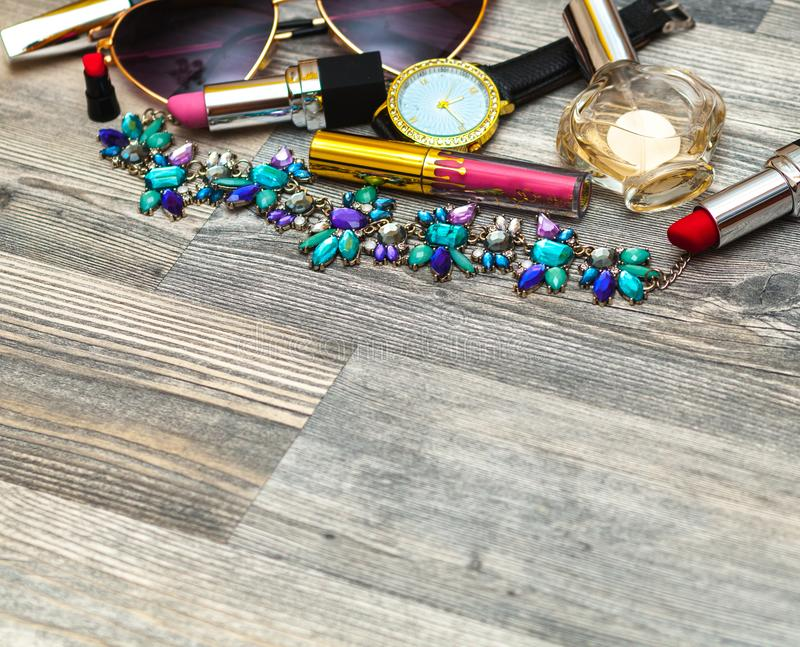 Flatlay féminin stylisé avec les verres, le rouge à lèvres, le parfum, la montre, le pendant, la chemise rayée et la moquerie sur photos libres de droits