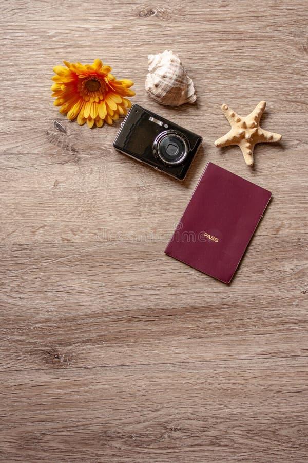 Flatlay ferie/travel tema med brun bakgrund med kameran, passet, skalet, sjöstjärnan och blommor royaltyfri foto