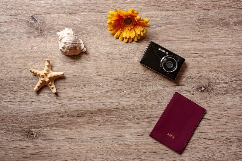 Flatlay ferie/travel tema med brun bakgrund med kameran, passet, skalet, sjöstjärnan och blommor royaltyfri bild