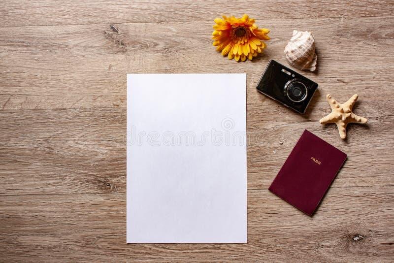 Flatlay ferie/travel tema med brun bakgrund med kameran, passet, skalet, sjöstjärnan och blommor royaltyfria bilder