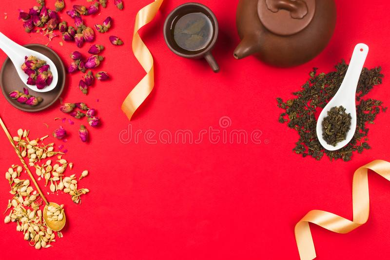 Flatlay frame arrangement with Chinese green tea, rose buds, jasmine flowers and golden ribbons royalty free stock image