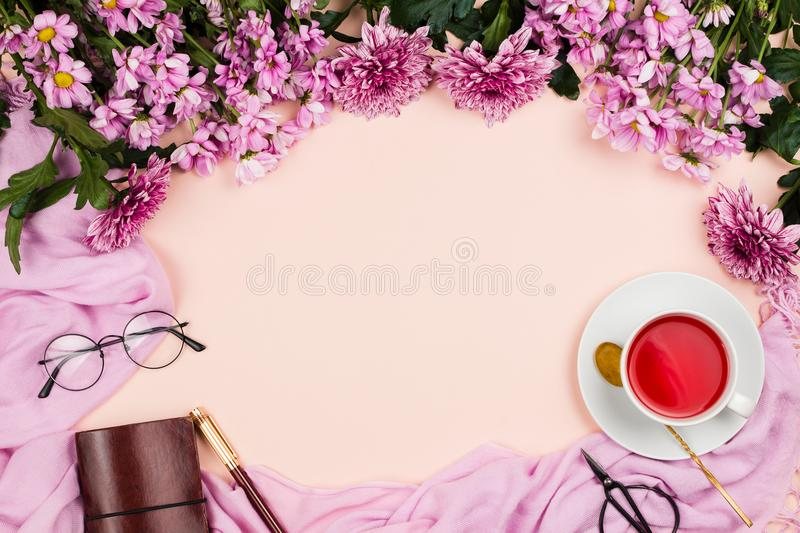 Flatlay frame arrangement with pink chrysanthemum flowers, hibiscus tea, pink scarf, glasses and notebook royalty free stock image