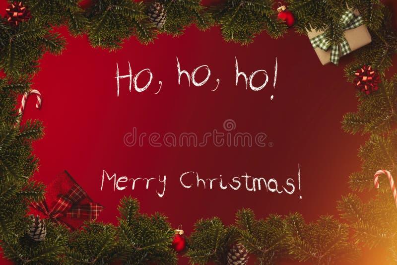 Flatlay gräns för glad jul med slågna in gåvor, röda bollar, rottingar, pilbågar, kotte fotografering för bildbyråer