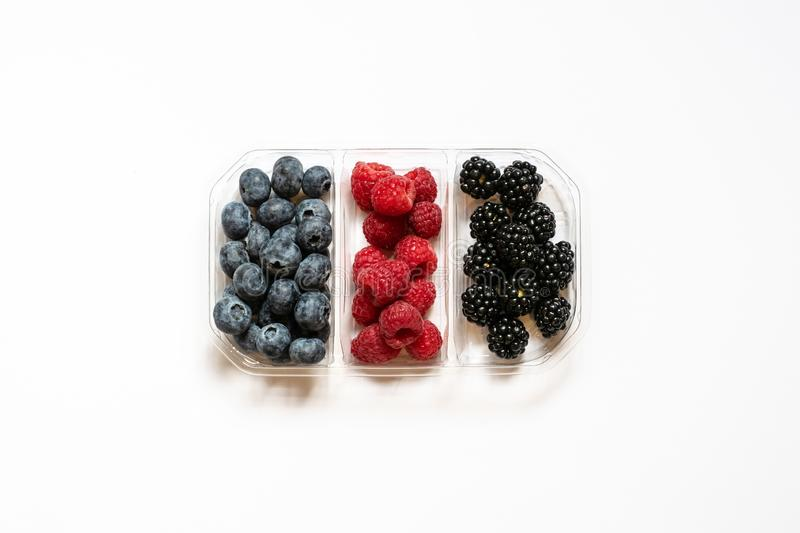 Flatlay group of fresh blueberries, raspberries and blackberries in a transparent plastic container isolated in a white background royalty free stock photos