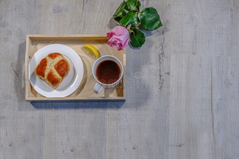 Flatlay ha sparato di un vassoio che tiene una tazza di tè, la fetta di limone e un panino trasversale caldo su un piatto Un osse fotografie stock libere da diritti