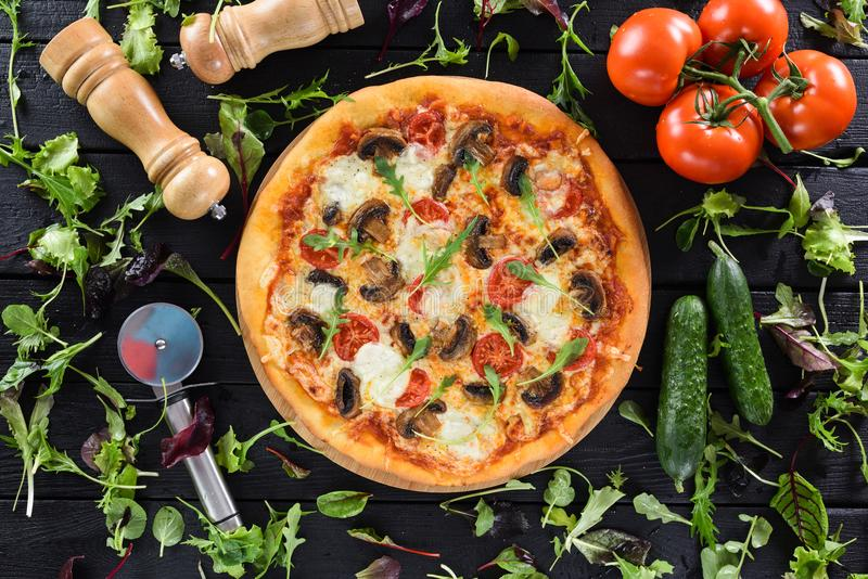 Flatlay of healthy vegetable mushroom pizza served with fresh vegetables, greens, pizza cutter and salt shaker on black background stock photography