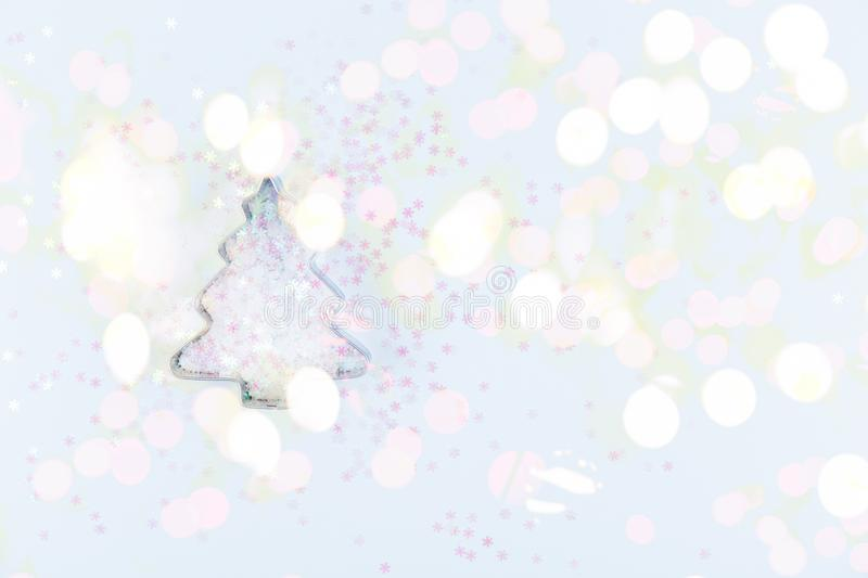 Flatlay with holiday tree cookie cutter and snowflake sprinkles on blue background. Holiday, Christmas and New Year concept. Cozy stock photography