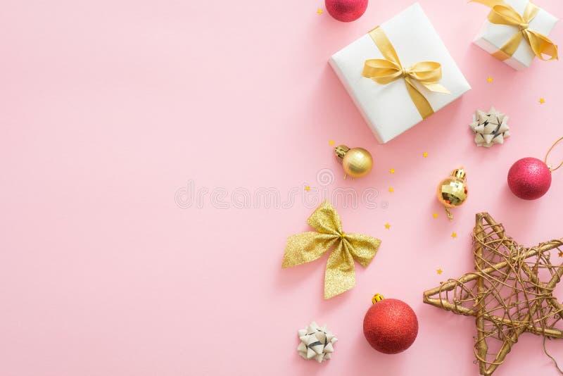 Flatlay kerstvakantie samenstelling op pastelroze achtergrond met exemplaarruimte Bovenaanzicht Xmas-versieringen, rode en gouden royalty-vrije stock afbeeldingen