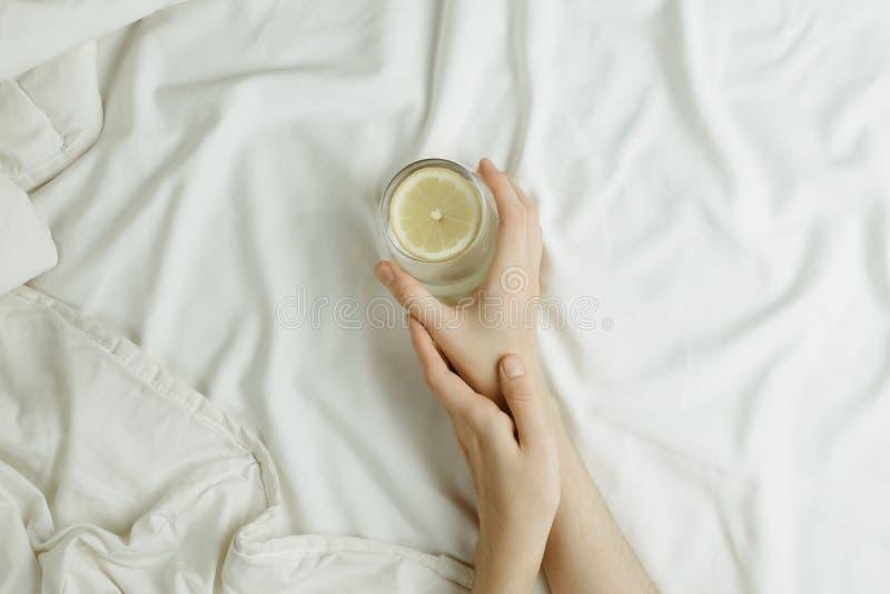 Flatlay kobiety ` s wręcza trzymać szklany w cytryny wodzie w łóżku na białych prześcieradłach zdjęcie stock