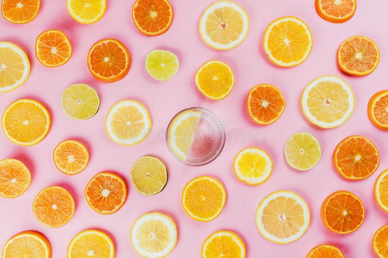 Flatlay of lemon water on pink background with various sliced citrus fruits stock photography