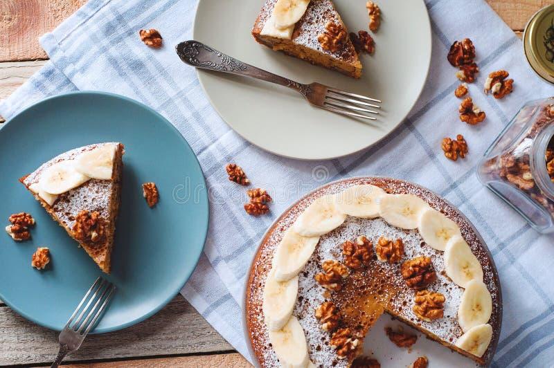 Flatlay med den skivade banankakan med den pudrade socker och valnöten på plattan med gaffel- och exponeringsglaskruset mycket av royaltyfri bild