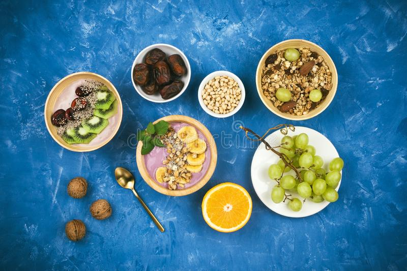 Flatlay med den sunda strikt vegetarianfrukosten av den vegetabiliska yoghurten för bäret bowlar med granola, chiafrö, olika fruk arkivbild