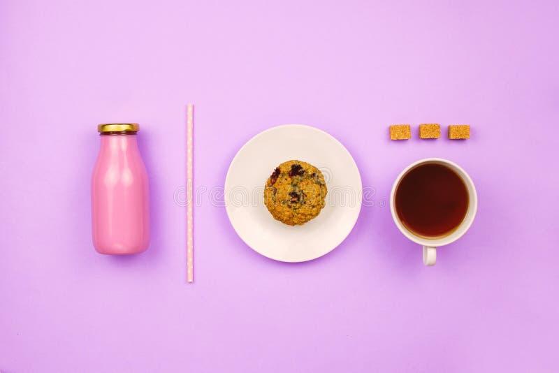 Flatlay med en blåbärmuffin, en kopp te, kuber för rottingsocker och en flaska av fruktsaft eller smoothien med ett sugrör arkivbilder