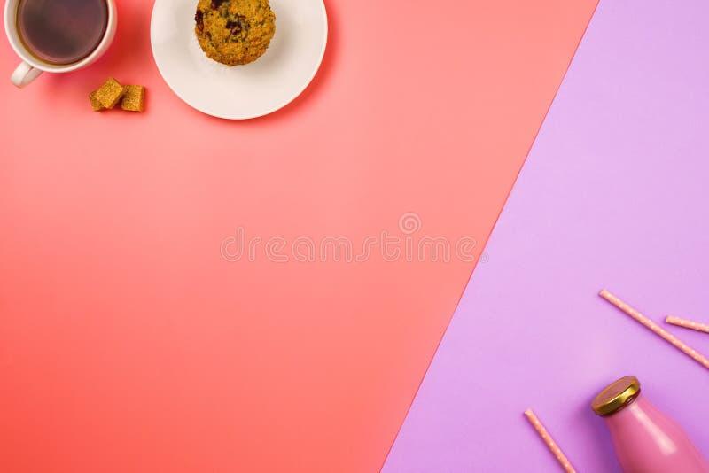 Flatlay med en muffin och en kopp te på en sida och en flaska för blåbär av fruktsaft eller smoothien med sugrör på den motsatta  arkivbild