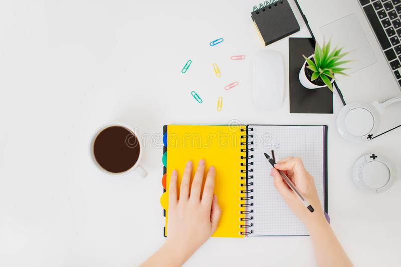 Flatlay med kvinnliga händer som skriver i en notepad royaltyfria foton