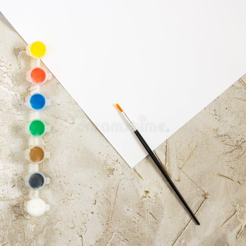Flatlay med ljusa målarfärger, borsten och det vita arket av papper på grå cementbakgrund, Workspace, konstnär, teckning, hobby,  arkivfoton
