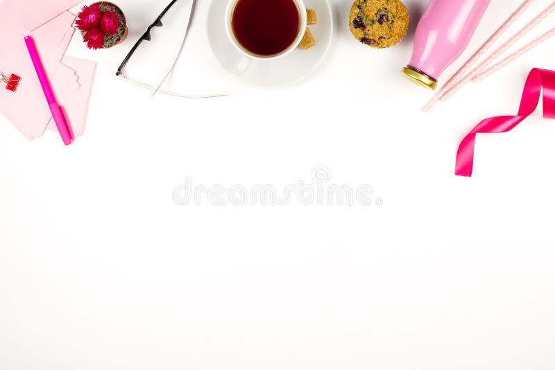 Flatlay med rosa anmärkningspapper, exponeringsglas, muffin, kopp te och flaskan av fruktsaft Begrepp av sund lunch på arbete royaltyfri bild