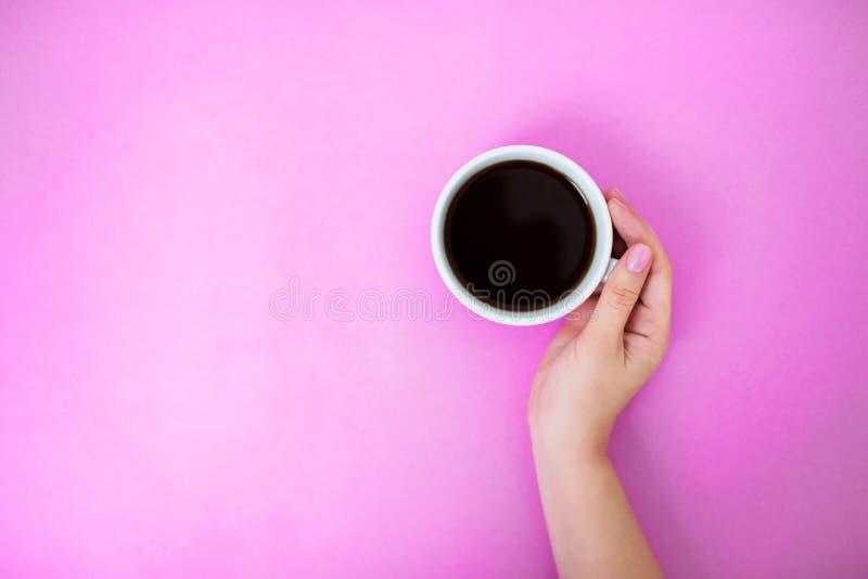 Flatlay met de koffiemok van de vrouwenholding met één hand stock afbeeldingen