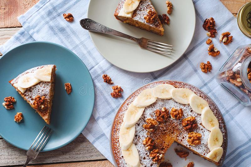 Flatlay met gesneden banaancake met gepoederde suiker en okkernoot op plaat met vork en glaskruikhoogtepunt van noten Comfortabel royalty-vrije stock afbeelding