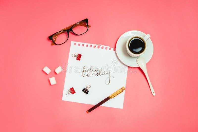 Flatlay met glazen, pen, klemmen, kop van koffie en witte pagina met het handlettering ` Hello Maandag ` royalty-vrije stock afbeelding