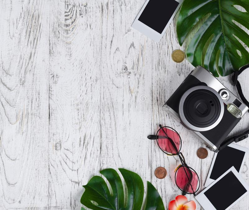 Flatlay mit Kamera, leeres Foto, Münzen, Sonnenbrille, Blätter auf t lizenzfreies stockfoto
