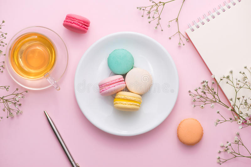 Flatlay of notebook, cake macaron, cup of tea and flower on pink stock image