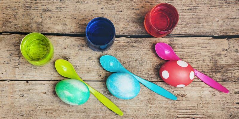 Flatlay, ovos da páscoa coloridos, tinturas do ovo e colheres na tabela de madeira imagem de stock royalty free