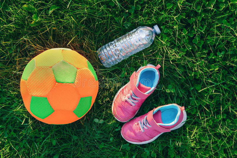 Flatlay with pair of pink girl sneakers shoes, child fabric soft soccer ball and bottle of water in green grass stock images